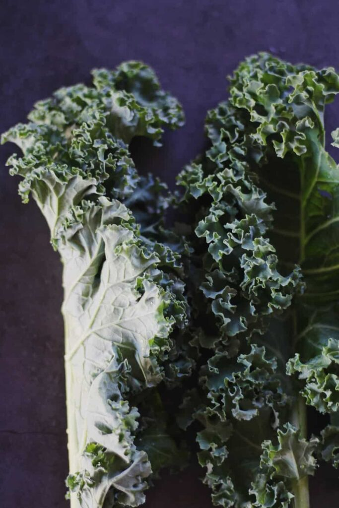 raw kale laying on counter for autumn kale salad