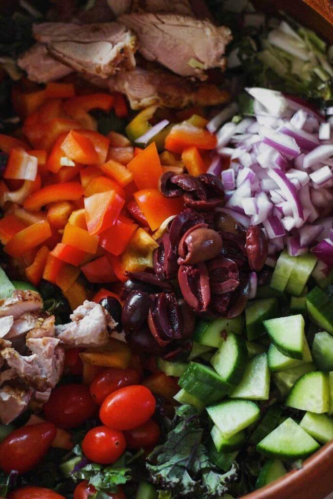 closeup shot of vegetables in kale greek salad with garlic tahini dressing
