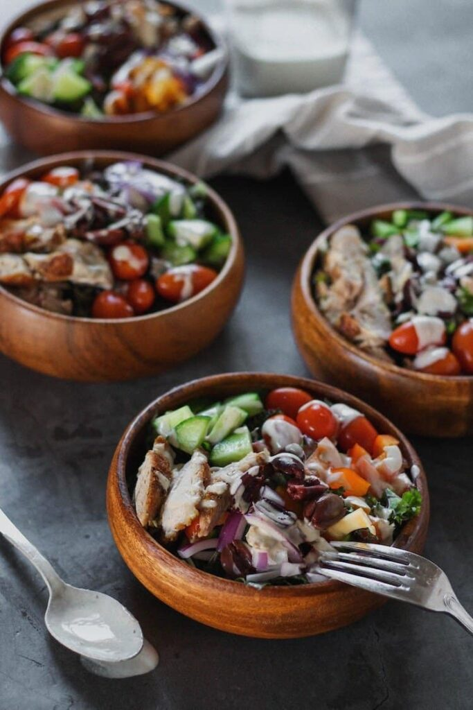 kale Greek salad served in wooden bowls with dressing in background