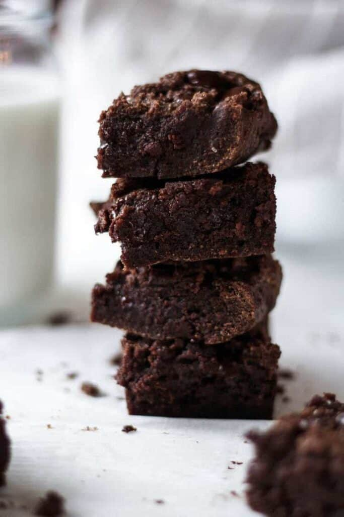 keto brownies stacked with glass of milk behind