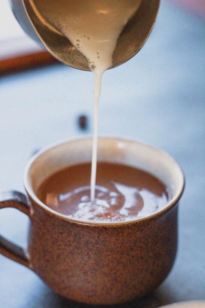 almond milk poured into mug of keto hot chocolate