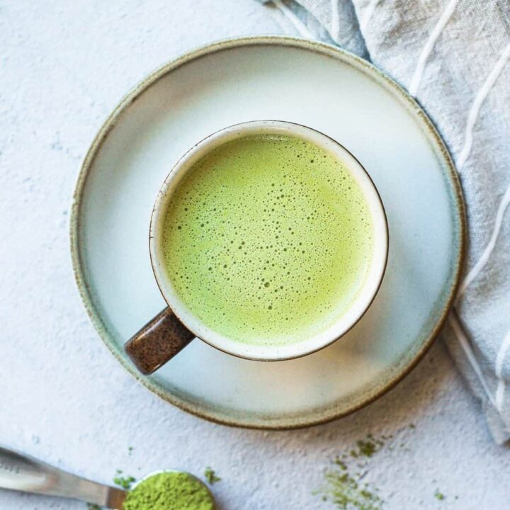 bulletproof matcha in a mug with a teaspoon of matcha next to it