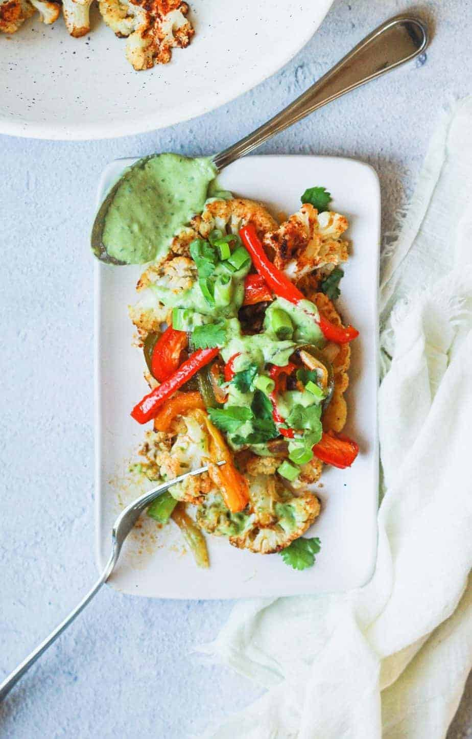overhead of fajita cauliflower steak with cilantro avocado dressing on a plate