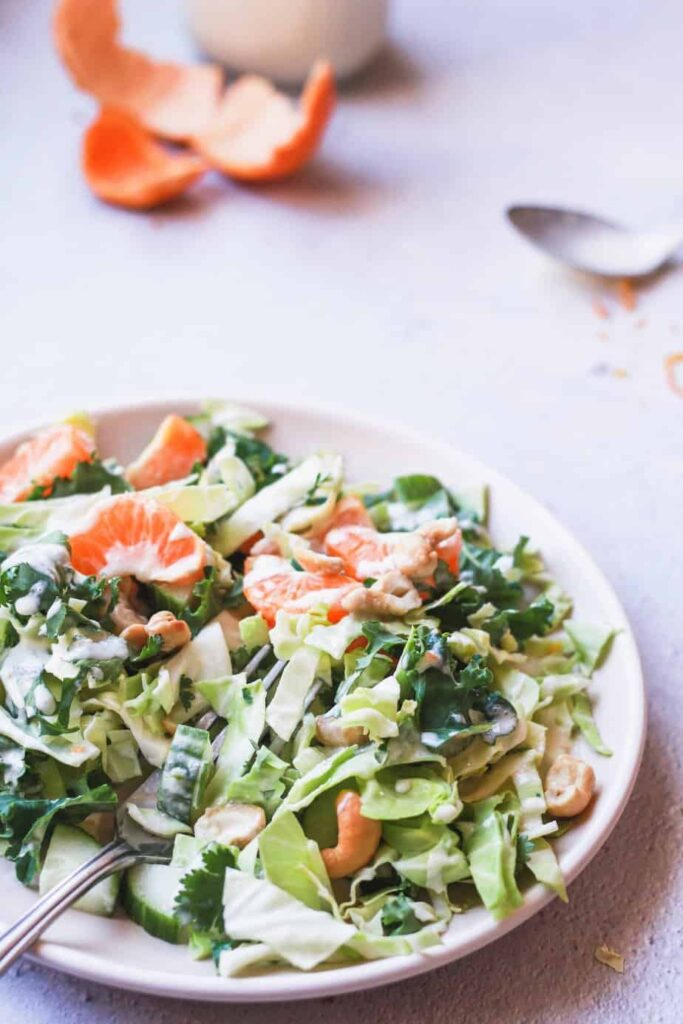 chopped cabbage salad with orange peel and dressing in background