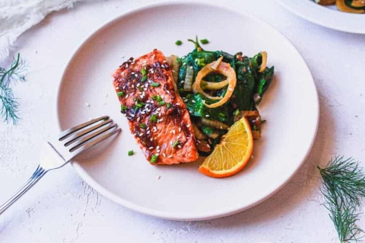 ginger soy salmon with sauteed spinach on a plate with a fork