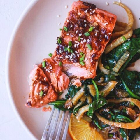 overhead of ginger soy salmon on a plate with sauteed spinach and fennel
