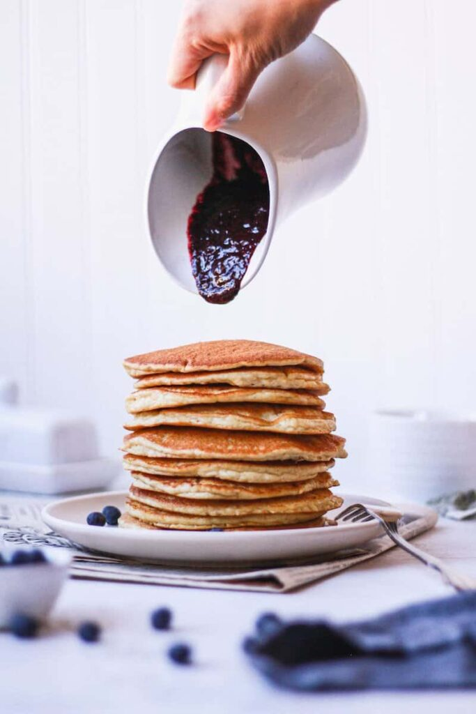 pouring blueberry sauce on a stack of keto almond flour pancakes