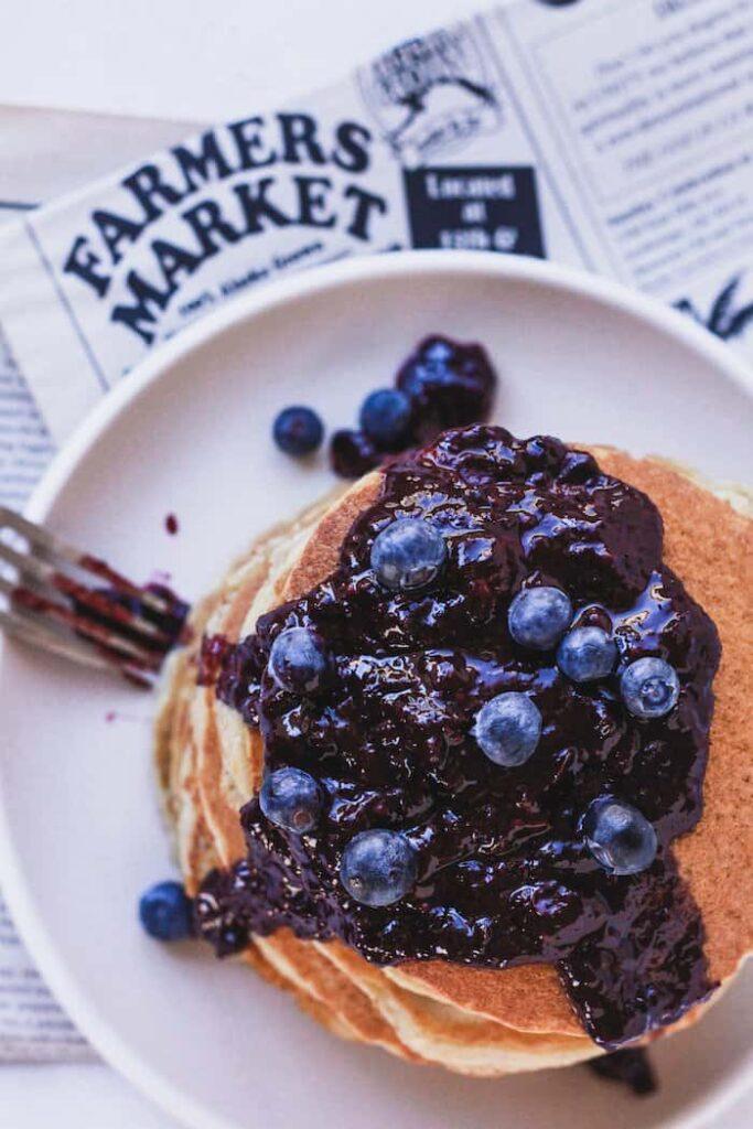 overhead of keto almond flour pancakes with blueberry sauce