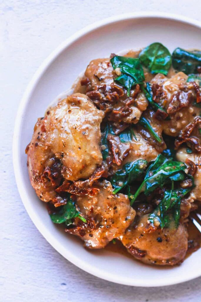 overhead of sun-dried tomato chicken on a round plate