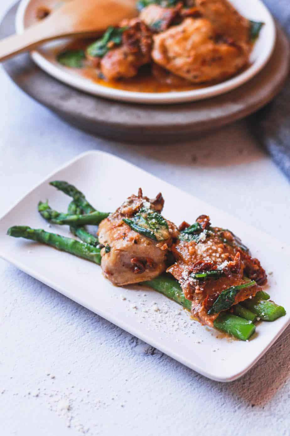 shot of sun-dried tomato chicken on plate with asparagus