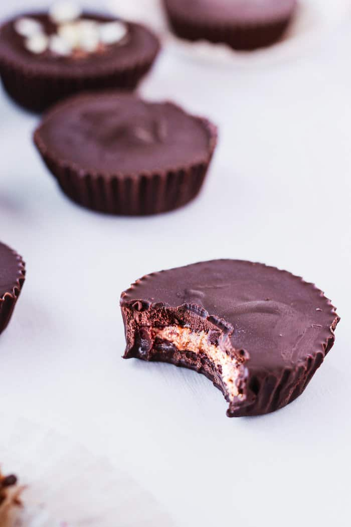 dark chocolate almond butter cup with a bite taken out of it