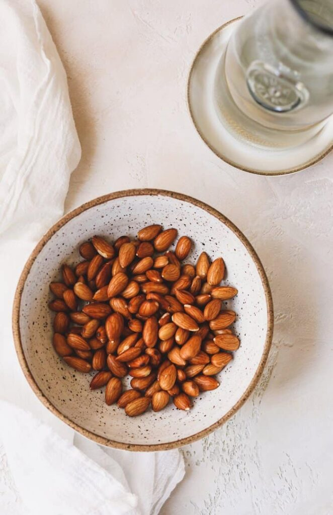 bowl of soaked almonds and a pitcher of water