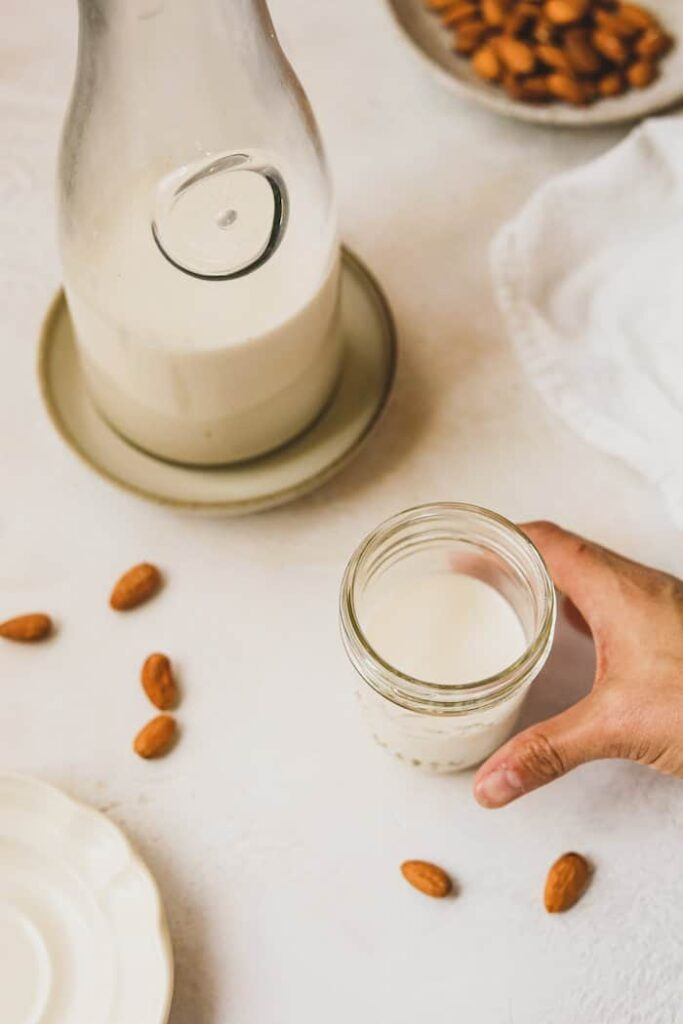 a pitcher and a glass of homemade almond milk
