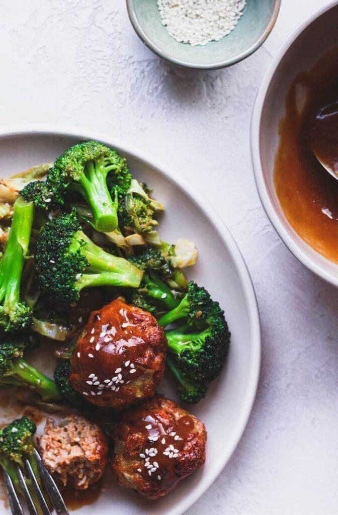 overhead of keto teriyaki chicken meatballs and broccoli on a plate