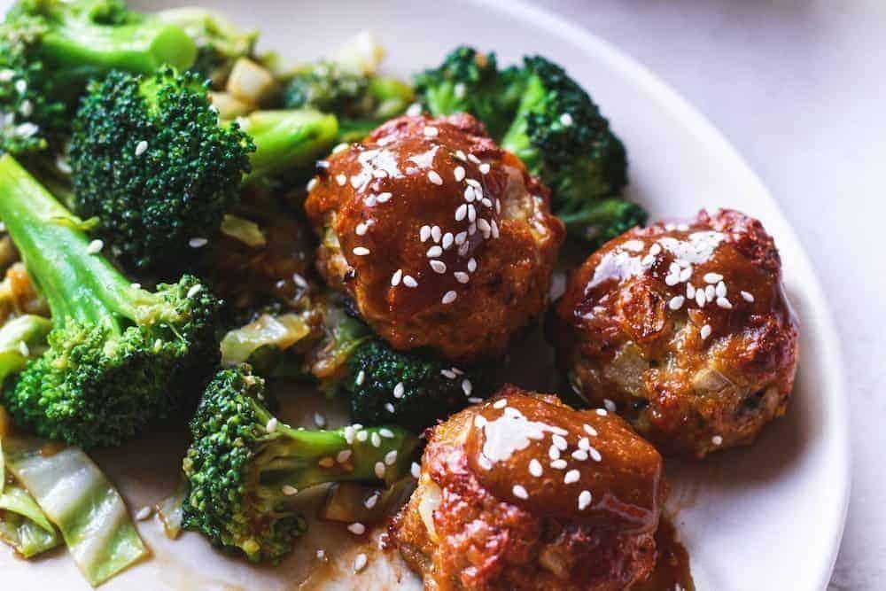 closeup of teriyaki chicken meatballs and broccoli on a plate