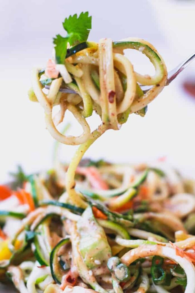bite of zucchini noodle salad with spicy peanut sauce