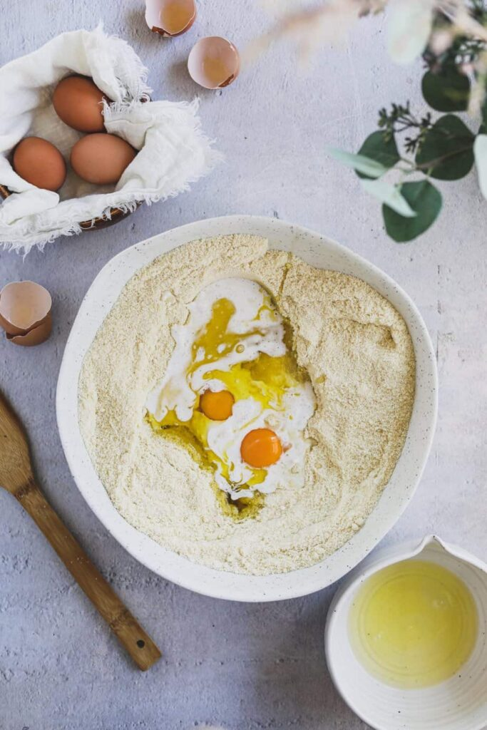 overhead of almond flour and eggs in a large bowl with a spoon