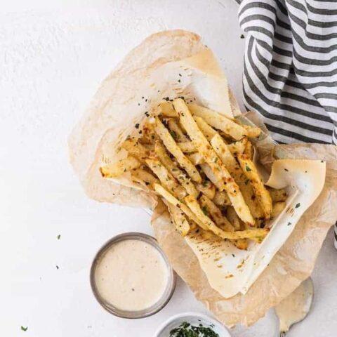 overhead of jicama fries in a basket with garlic aioli and cilantro