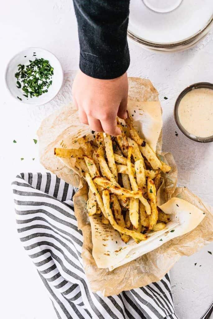 hand reaching to grab a cilantro garlic jicama fry