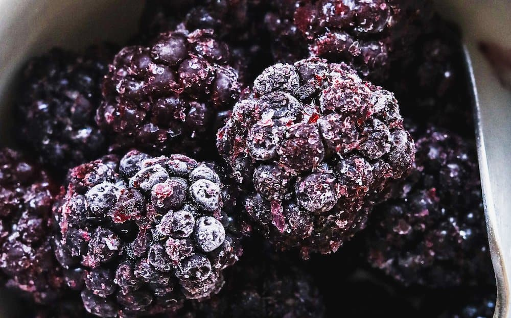 closeup of frozen blackberries for keto cake trifle