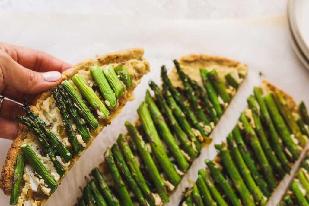 holding a slice of keto ricotta and asparagus flatbread