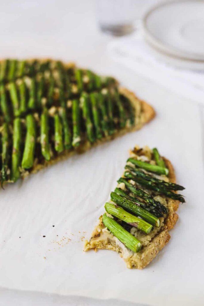 a slice of keto ricotta and asparagus flatbread