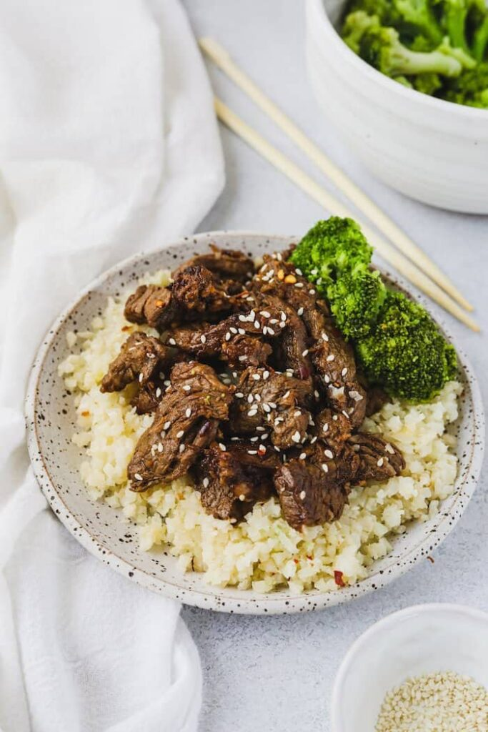 Low-carb beef bulgogi on a plate with cauliflower rice and broccoli
