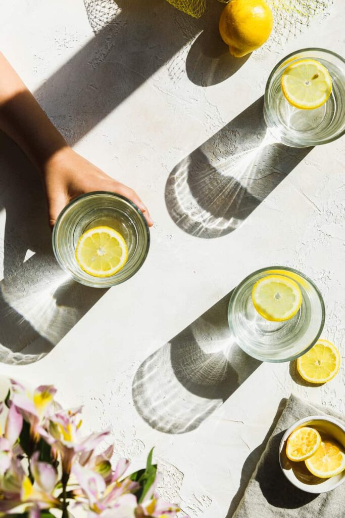 lemon waters in a glass with a hand reaching for one