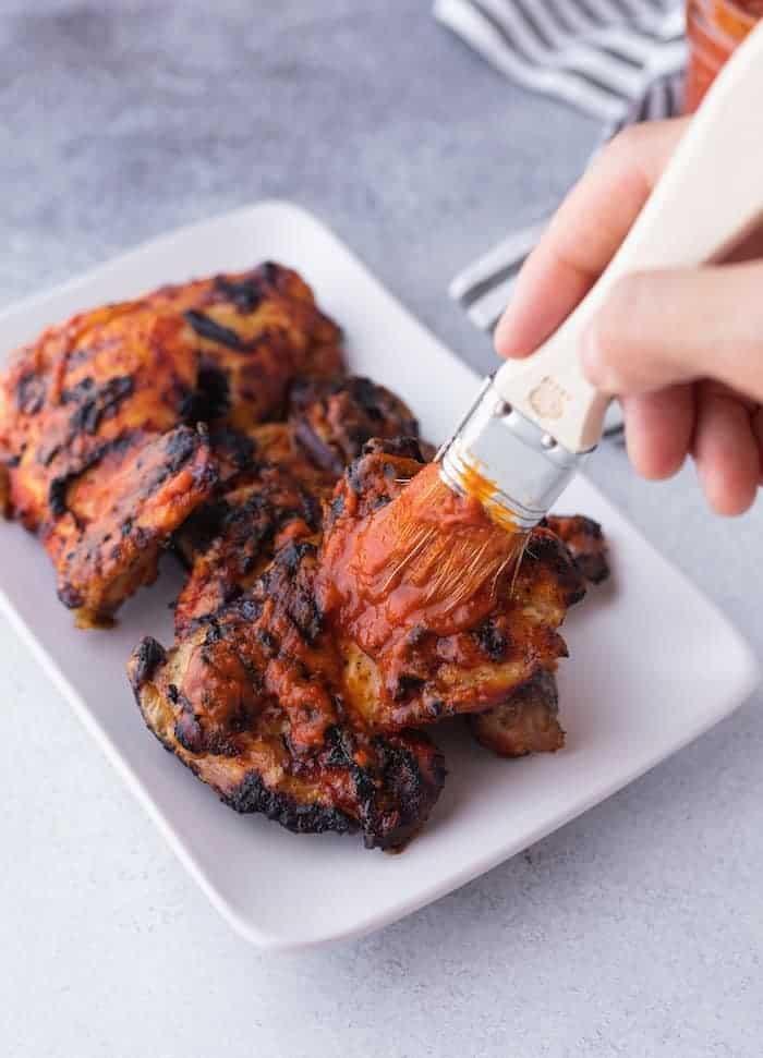brushing keto bbq sauce on chicken