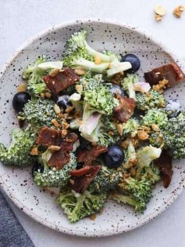 keto broccoli salad with bacon on a plate with a blue napkin and fork