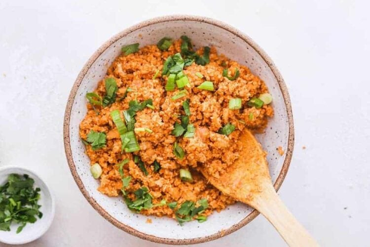 spanish cauliflower rice in a serving bowl with wooden spoon
