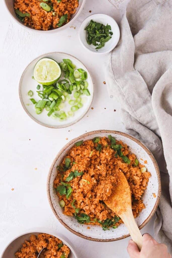 spanish cauliflower rice in bowls with toppings in side dish