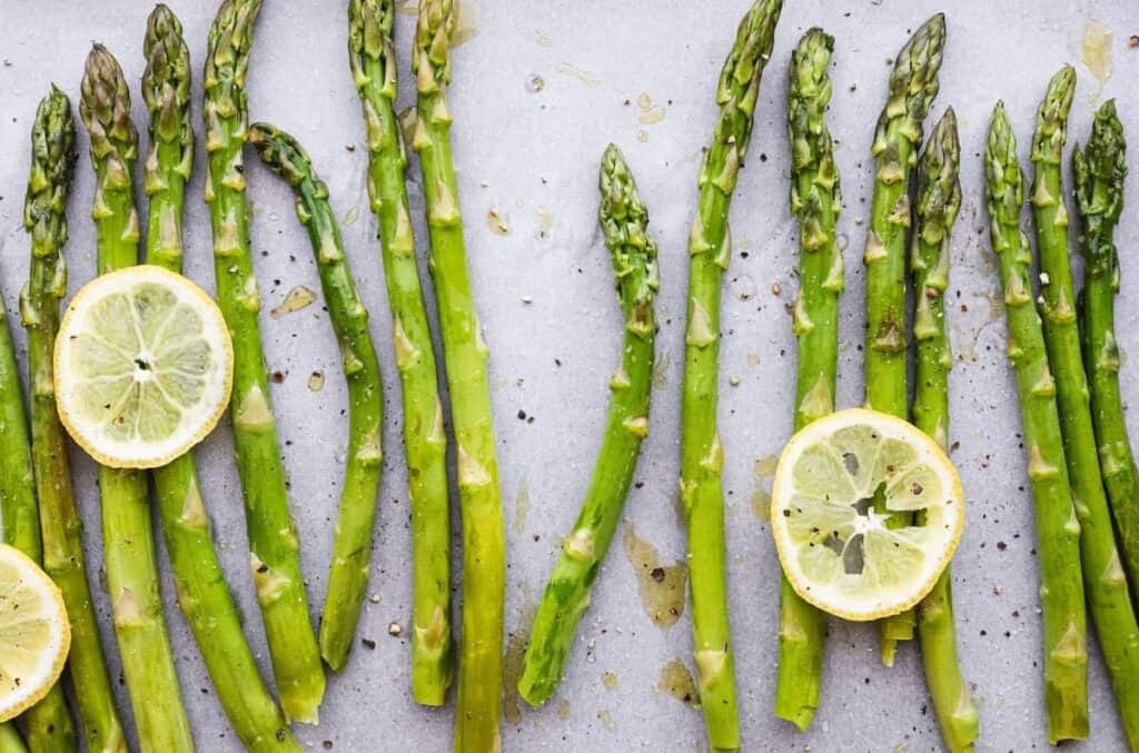 roasted asparagus on a baking sheet with lemon slices