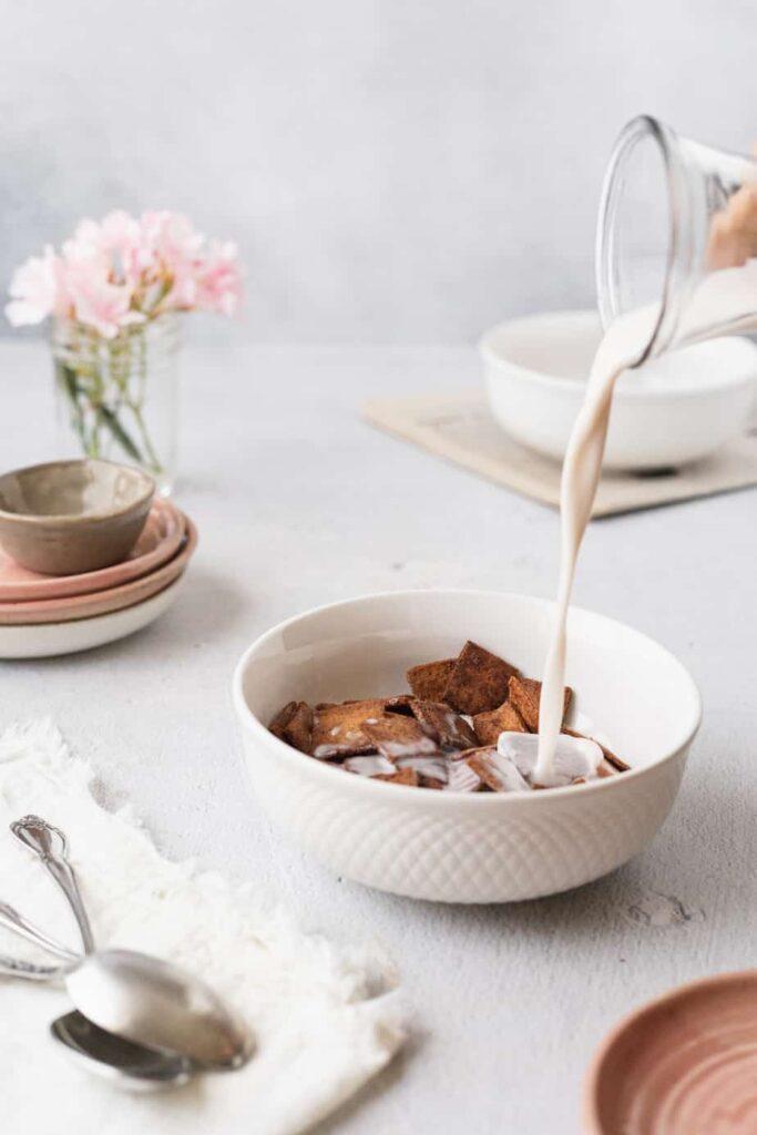 pouring macadamia milk over keto cinnamon toast crunch cereal