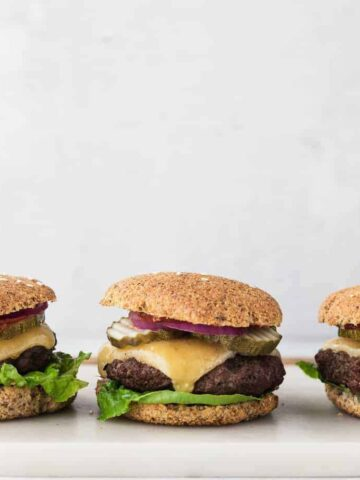 three low-carb burgers on a cutting board lined up