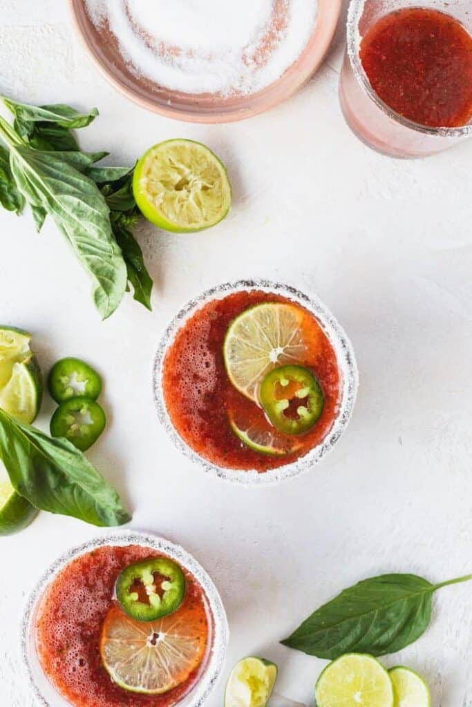 wide overhead of glasses of keto strawberry basil margaritas