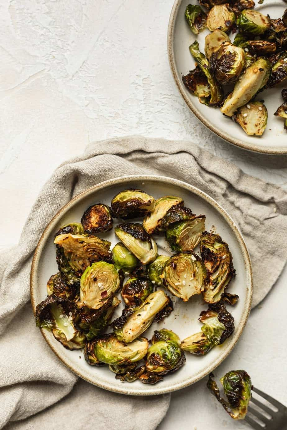 two plates with air fryer brussels sprouts and a fork
