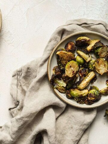 overhead of air fryer brussels sprouts with miso on a plate with a linen napkin and water glass