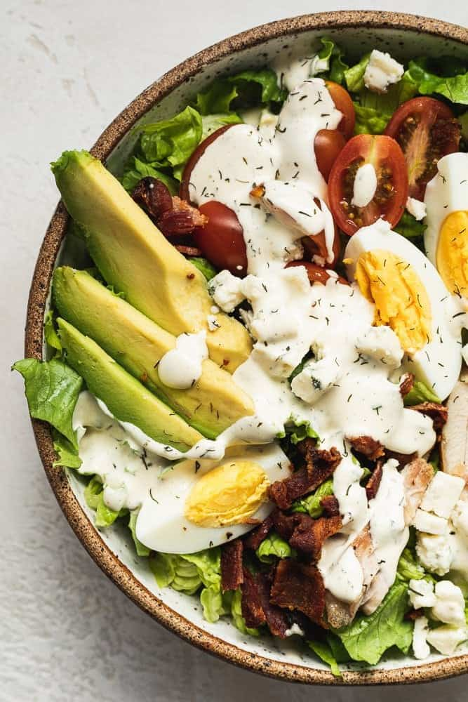 closeup of avocado and keto Cobb salad ingredients with dressing