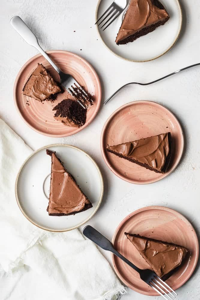 vertical shot of keto chocolate cake slices on pink and white plates with forks