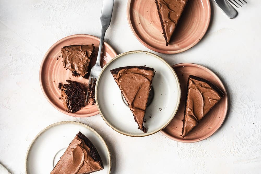 overhead of five plates with slices of keto chocolate cake