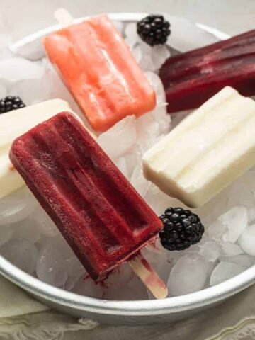three flavors of keto popsicles on ice in a cake pan