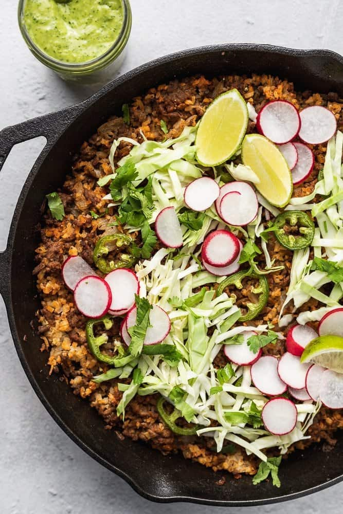 Overhead of keto taco casserole with fresh vegetable toppings
