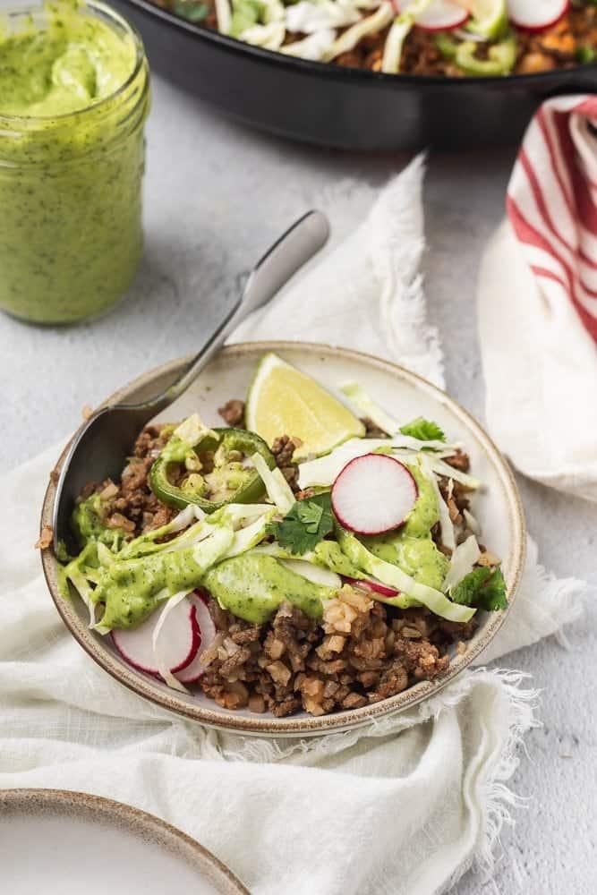 a plate of keto taco casserole topped with avocado cilantro dressing