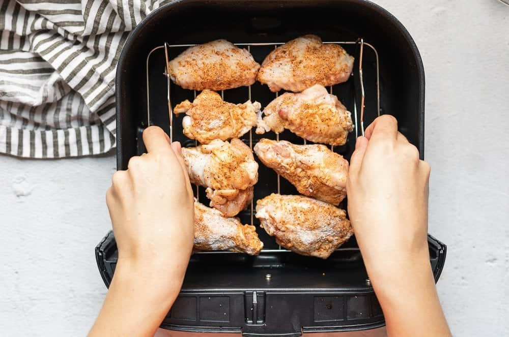 chicken wings on a rack placed into air fryer basket