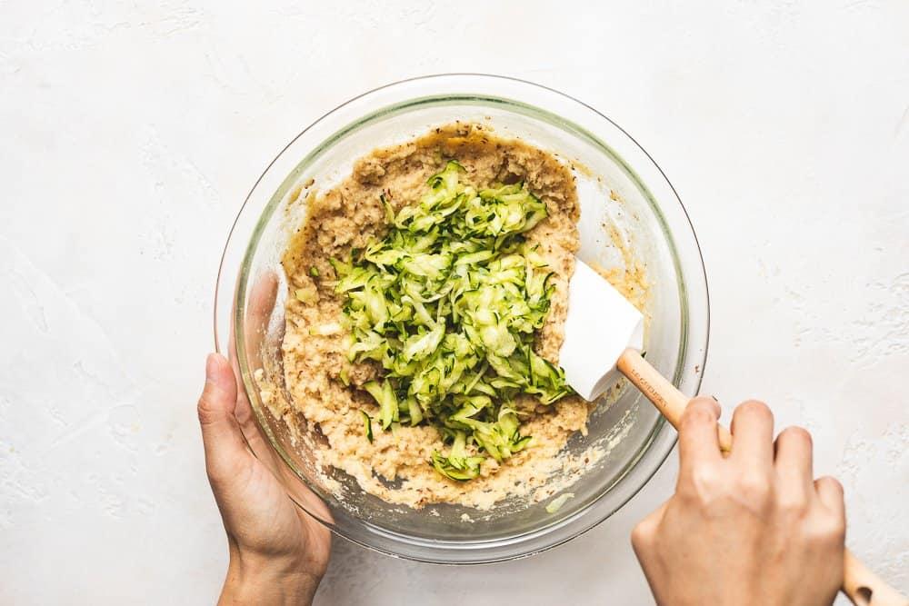 stirring zucchini into keto zucchini bread batter