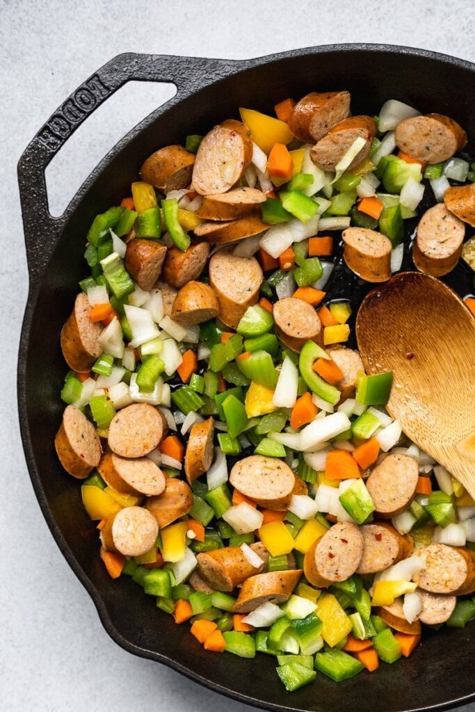 veggies and sausage in a cast iron skillet