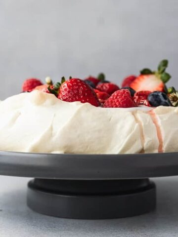 straight on shot of keto pavlova with toppings on a cake stand