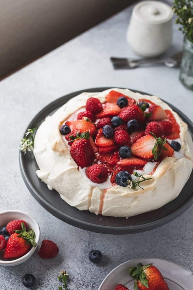 keto pavlova with berries on a cake stand