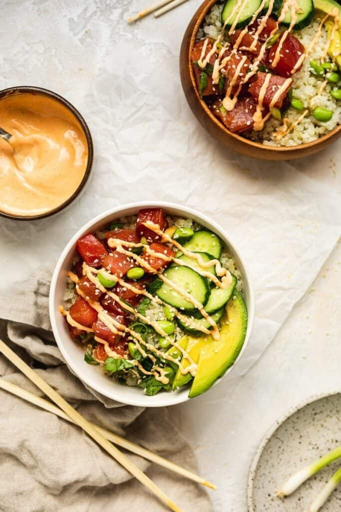 two keto poke bowls with chopsticks and spicy mayo